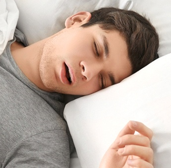 A young male wearing a gray t-shirt and breathing through his mouth while asleep