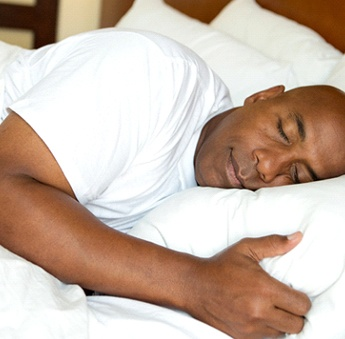 A middle-aged man wearing a white t-shirt and sleeping with the help of relaxation techniques