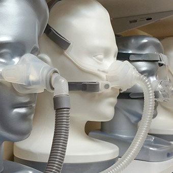 Wooden models wearing different CPAP masks
