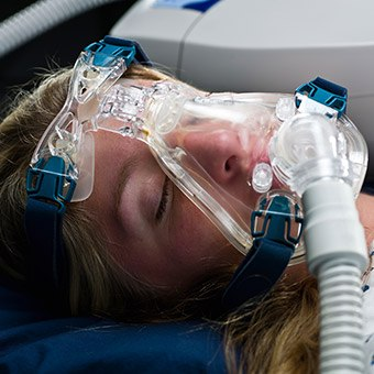 Woman with full face CPAP mask in place