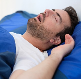 Man in bed sleeping with mouth open