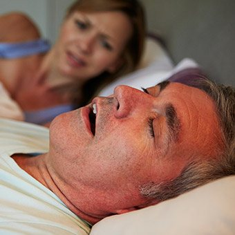 Woman frustrated in bed with snoring man